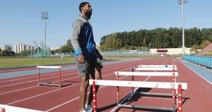 Черный мужской спортсмен делая тренировки с препонами outdoors видеоматериал