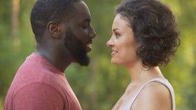 Черный мужчина и белая женщина чувствительно касаются носам и усмехаются счастливо потом видеоматериал