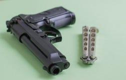 Черный нож пистолета и утюга на салатовой предпосылке Стоковое Фото