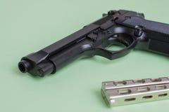 Черный нож пистолета и утюга на салатовой предпосылке Стоковые Фото