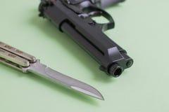 Черный нож пистолета и утюга на салатовой предпосылке Стоковое Изображение
