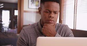 Черный парень работая на его компьтер-книжке Стоковые Фотографии RF