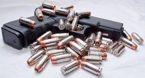 Черный пистолет с пулями на ем и рядом с ним Стоковая Фотография RF