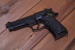 Черный пистолет на деревянной предпосылке Стоковые Фото
