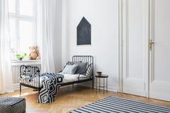 Черный плакат над кроватью со сделанными по образцу листами стоковые изображения