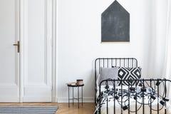Черный плакат на белой стене над кроватью в простом интерьере спальни с дверью и таблицей стоковое фото rf