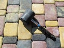 Черный резиновый молоток лежит на поверхности свеже вымощенного пестротканого вымощая сляба, конце-вверх, взгляд сверху стоковая фотография