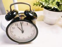 Черный ретро будильник на белых таблице и цветочном горшке стоковые изображения