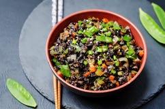 Черный рис с щелчковыми горохами и овощами на черноте Стоковые Фотографии RF