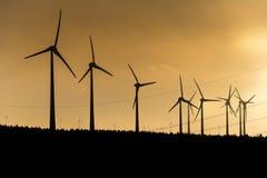 Черный силуэт генератора энергии windturbines на изумительном заходе солнца на ветровой электростанции в Германии Стоковые Фотографии RF