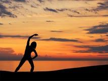 Черный силуэт женщины делая тренировку на заходе солнца Стоковое Фото