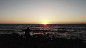 Черный силуэт женщины на скалистых руках пляжа моря распространил wite во время захода солнца над океаном с волнами ударяя пляж В сток-видео