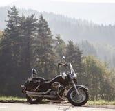 Черный сияющий высокоскоростной мотоцикл припаркованный на пустой узкой обочине страны на солнечный летний день стоковые фотографии rf