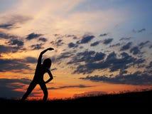 Черный силуэт женщины делая тренировку на заходе солнца Стоковое фото RF