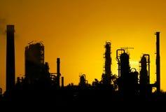 Черный силуэт станции рафинадного завода сырой нефти во время захода солнца Стоковое Изображение