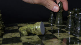 Черный слон в шахмат наносит поражение белой лошади Деталь шахматной фигуры на черной предпосылке Игра шахмат крупного плана eyed Стоковое фото RF