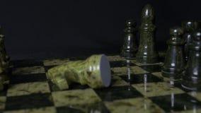 Черный слон в шахмат наносит поражение белой лошади Деталь шахматной фигуры на черной предпосылке Игра шахмат крупного плана eyed Стоковые Фотографии RF
