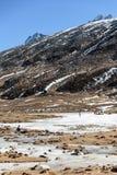 Черный снег witn горы и ниже с туристами на том основании с коричневой травой, снегом и замороженным прудом в зиме на zero этап Стоковое Фото