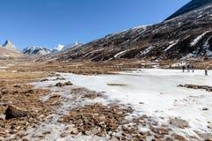 Черный снег witn горы и ниже с туристами на том основании с коричневой травой, снегом и замороженным прудом в зиме на zero этап Стоковые Фотографии RF