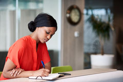 Черный студент делая примечания в ее тетради сидя дома Стоковая Фотография