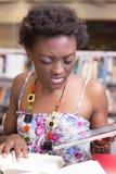 Черный студент используя ее таблетку пока изучающ Стоковые Изображения
