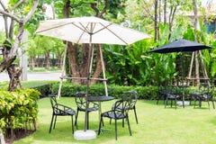 Черный стул стола под белым зонтиком на траве в ga Стоковые Фотографии RF