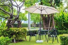 Черный стул стола под белым зонтиком на траве Стоковое Изображение RF