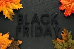 Черный текст пятницы с листьями осени на черном шифере стоковые фотографии rf