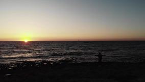 Черный темный силуэт человека стоя на пляже со смотреть оружий широкий открытый к заходу солнца над океаном с маленькой лодкой на акции видеоматериалы