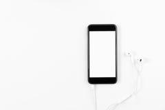 Черный телефон и белые наушники на белой предпосылке Технологические концепции делают прогресс Стоковое фото RF