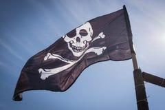 Черный флаг пирата развевая на ветре на предпосылке голубого неба Стоковые Фотографии RF