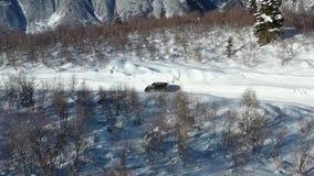 Черный фургон управляет на дороге покрытой снегом около деревьев на с видеоматериал