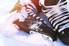 Черный хоккей катается на коньках лежащ в снеге и ярком солнце стоковое фото rf