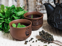 Черный чайник с зеленым чаем и чашка для чая Стоковые Фотографии RF