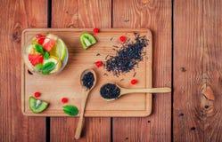 Черный чай с в деревянными ложками на деревянной доске украсил w Стоковое фото RF
