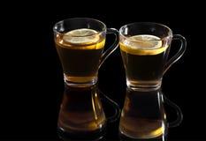 Черный чай с лимоном в стеклянной чашке, с отражением на черной предпосылке стоковое изображение rf