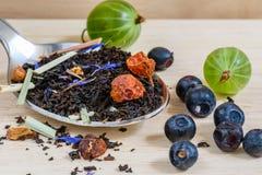 Черный чай с различными плодоовощами и ягодами для завтрака стоковое фото