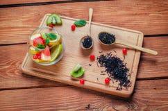 Черный чай с травами в деревянных ложках на decorat деревянной доски Стоковая Фотография