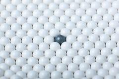 Черный шарик среди много белых одних Предпосылка шариков airsoft Стоковое Фото