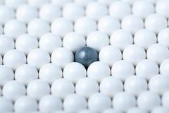 Черный шарик среди много белых одних Предпосылка шариков airsoft Стоковые Фото