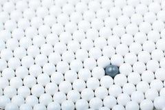 Черный шарик среди много белых одних Предпосылка шариков airsoft Стоковое Изображение RF