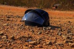 Черный шлем, который держат под горячим солнечным светом на грубой дороге стоковое изображение