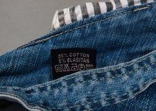 Черный ярлык ткани на крупном плане джинсов Ярлык одежды с инструкциями заботы прачечной Стоковые Изображения