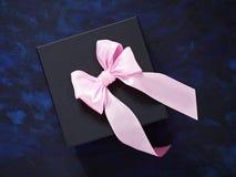 Черный ящик подарка стильный на сине-черной предпосылке Украшенное острословие Стоковая Фотография