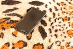 Черный smartphone на предпосылке кожи тигра Стоковая Фотография