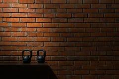 2 черных гантели для спорта в темной комнате против предпосылки кирпичной стены Стоковые Изображения RF