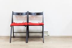 2 черных деревянных стуль с мягкими подушками близко стена Стоковое фото RF