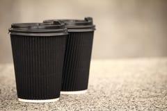 2 черных устранимых чашки кофе с крышками стоят на каменном парапете стоковые фотографии rf