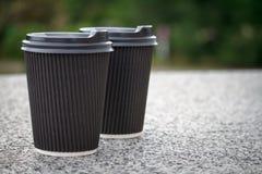 2 черных устранимых чашки кофе с крышками стоят на каменном парапете стоковое фото rf