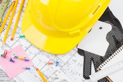 Чертежи, желтый шлем и инструменты конструкции, деревянная предпосылка Стоковое Изображение RF